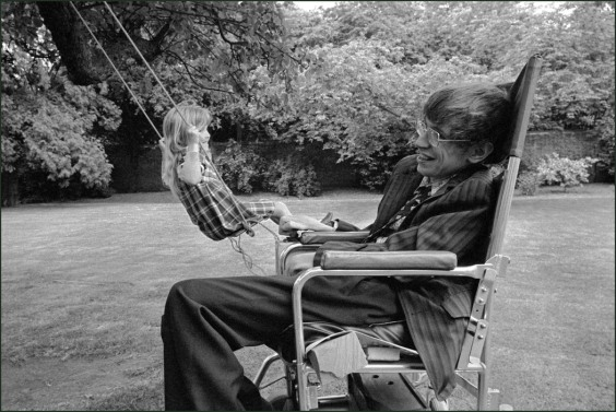 England. Cambridge. Professor Stephen Hawking in his garden with his daughter on a swing. 1977