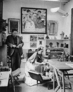 Diego Rivera and Frida Kahlo read and work in a studio.