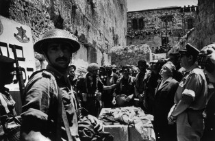 "East Jerusalem, 7th June 1967.In the course of the War of Independence in 1948, the Jewish Quarter of the Old City of Jerusalem was captured by the Jordanian ""Arab Legion"", and from then on Jewish worshippers were denied access to the Western Wall (also known as the Wailing Wall).The Israeli Paratroop Brigade burst into the Old City and from there descended to liberate the Western Wall. Israeli Prime Minister David BEN GURION witnessed the reclaiming of the Wailing Wall"
