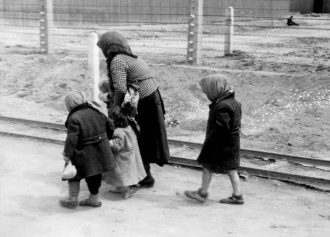 Auschwitz, summer 1944: elderly Jewish woman with young children on her way to the gas chambers