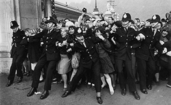 Excited Beatles fans are trying to keep London police in check on October 26, 1965 in front of Buckingham Palace.